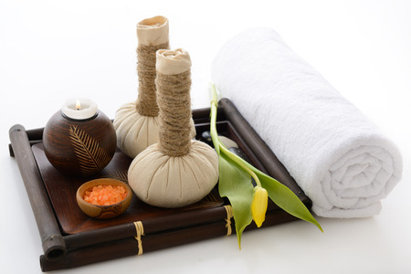 spa still life: spa still life with spa herbal balls, candlestick, tulip, stones and salt in wooden bowl and white towel over white