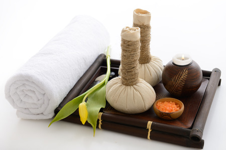 ayurvedic: spa still life with spa herbal balls, candlestick, tulip, stones and salt in wooden bowl and white towel over white