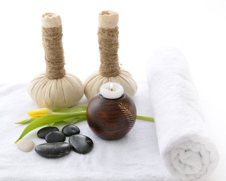 spa still life with spa herbal balls, candlestick, tulip, stones  in wooden bowl and white towel over white photo