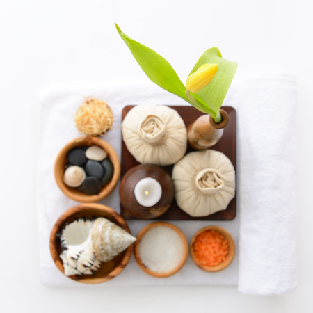 spa still life with spa herbal balls, candlestick, tulip, stones and salt in wooden bowl on white towel photo