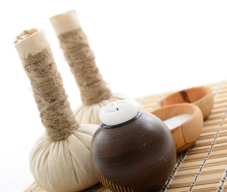spa still life with spa herbal balls, candlestick and salt in wooden bowl over white Stock Photo