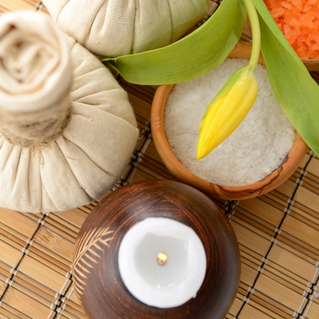 spa still life with spa herbal balls, candlestick, tulip, stones and salt in wooden bowl photo