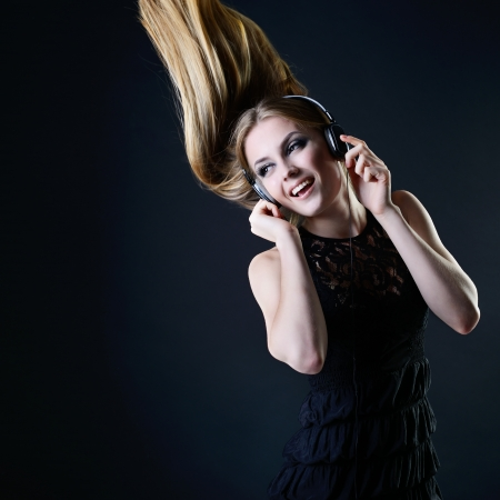 Music girl. Young beautiful excited woman with headphones listening music and dancing with long blond hair fly-away against dark background  photo