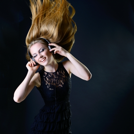 flyaway: Music girl. Young beautiful excited woman with headphones listening music and dancing with long blond hair fly-away against dark background