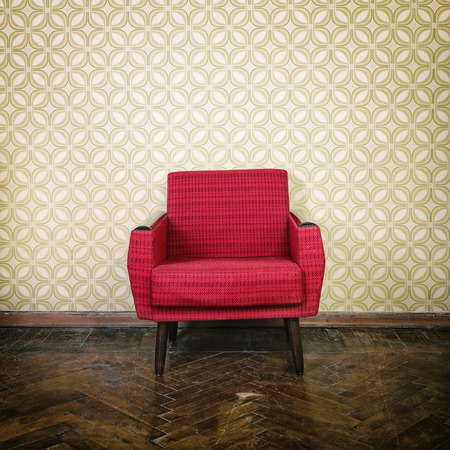 Vintage room with old fashioned red armchair, wallpaper and weathered wooden parquet floor photo