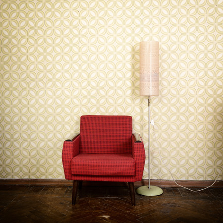 Vintage room with old fashioned armchair, standart lamp, old fashioned wallpaper and weathered wooden parquet floor photo