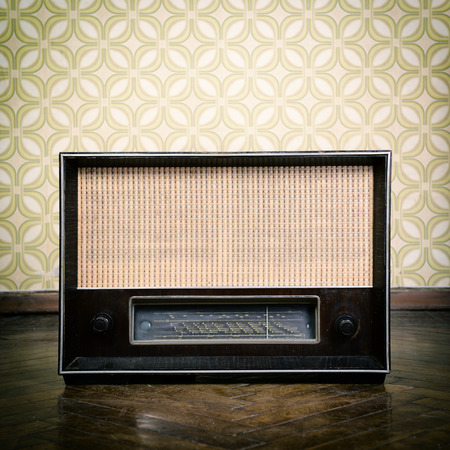 transistor: vintage radio receiver device on the weathered wooden parquet floor in vintage room with old fashioned wallpaper, toned