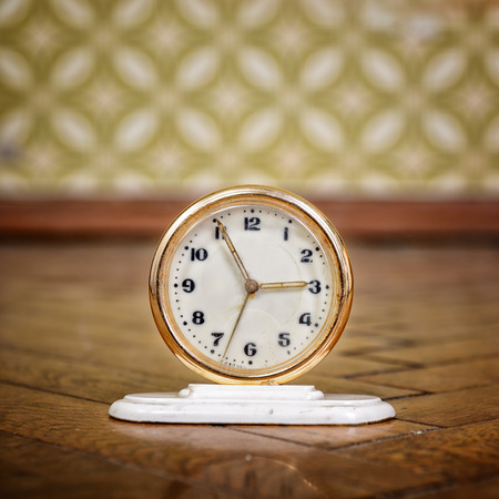 Retro clock on the weathered wooden parquet floor in vintage room with old fashioned wallpaper  photo