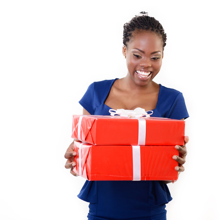 hedonistic: Joyful happy smiling young african woman holding red gift boxes, over white