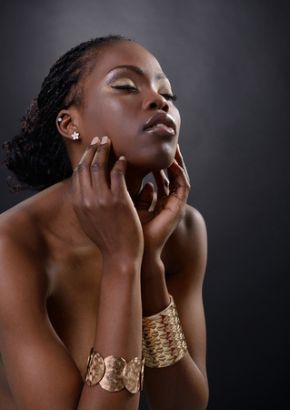 african american nude: Beautiful young african woman posing at studio in golden jewellery, face with hand portrait over dark background Stock Photo