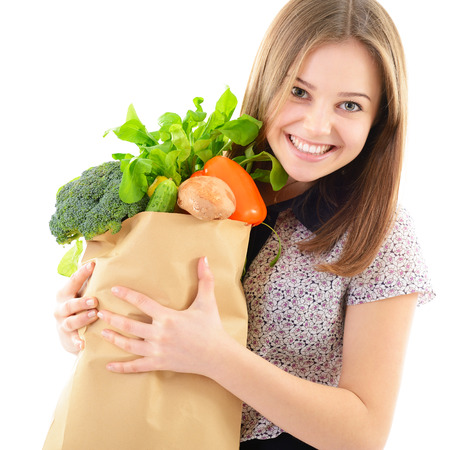 Portrait of a pretty teen girl holding a grocery bag and smiling against white background  Stock Photo