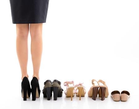 Shopping e vendita. Piedini femminili con scarpe assortimento, giovane donna mettere le scarpe in negozio e fa la sua scelta, vista posteriore. Più di sfondo bianco