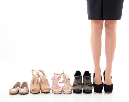 pies bonitos: Compras y venta. Piernas de mujer con zapatos de surtido, joven mujer puso los zapatos en la tienda y hace su elección, la vista frontal. Sobre fondo blanco