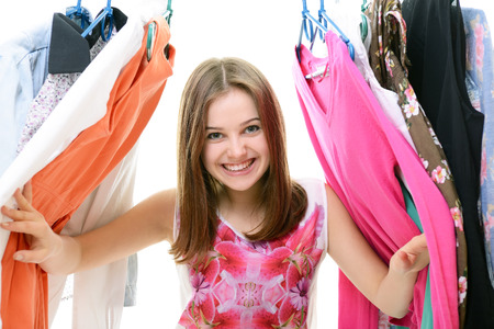 teenage girl dress: Portrait of a happy attractive teen girl making choices in wardrobe