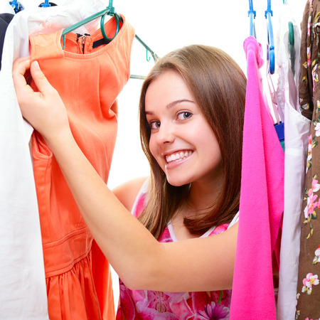 teenage girl dress: Portrait of a happy attractive teen girl making choices in wardrobe or in shop with clothes