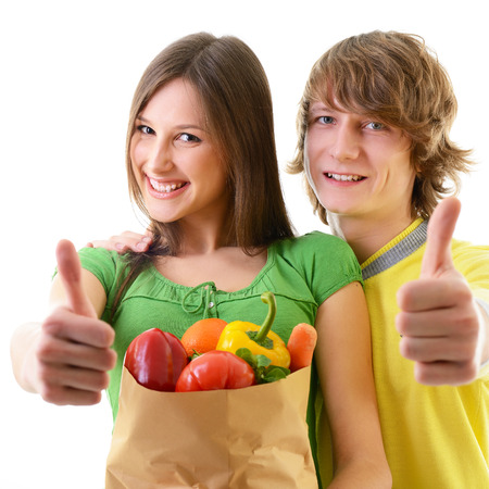 Portrait of a pretty young couple with thumbs up, holding a grocery bag and smiling against white background  photo