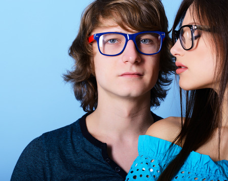 Fashionable young couple wearing trendy sunglasses, over blue Foto de archivo
