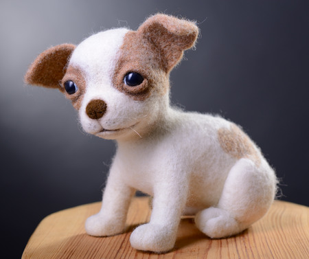 snugly: Toy dog, hand made puppy sitting in studio on wooden stool, felting  Stock Photo