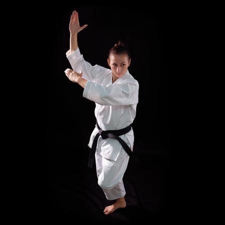 karate girl with black belt posing, champion of the world, on black background studio shot photo