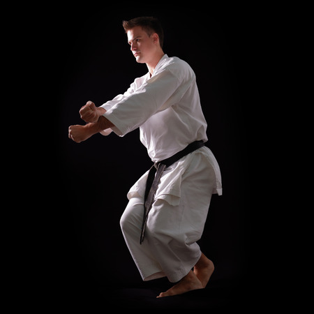black belt: karate man with black belt posing, champion of the world on black background studio shot