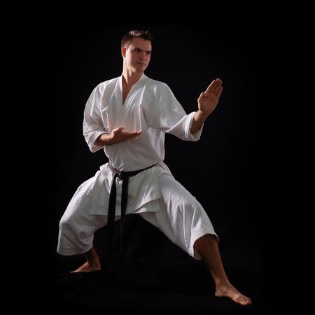 arts backgrounds: karate man with black belt posing, champion of the world on black background studio shot