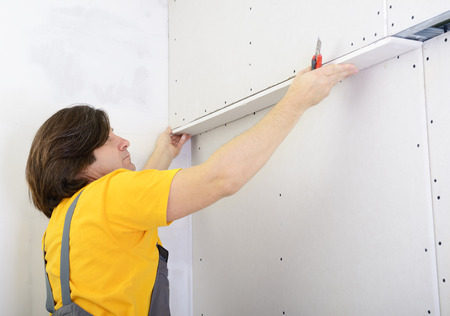 drystone: Man working with plasterboard, try on drywall panel to wall