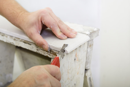 plasterboard: Man works with plasterboard, cut it with knife
