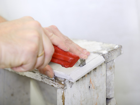 drystone: Man works with plasterboard, cut it with knife