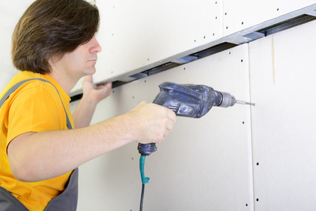 attach: Man using drill to attach drywall panel to wall Stock Photo