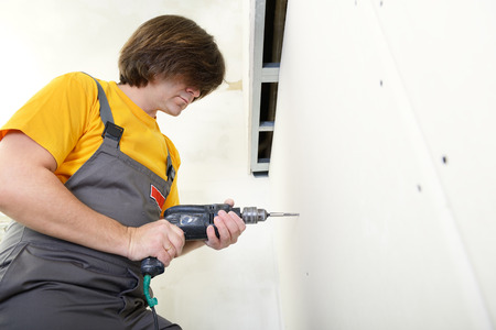 drystone: Man using drill to attach drywall panel to wall Stock Photo