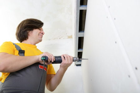 drystone: Man using drill to attach drywall panel to wall. Work with plasterboard