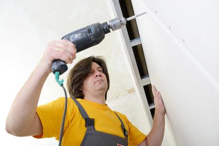 tablaroca: Hombre que usa el taladro para fijar el panel de yeso de la pared. Trabajar con planchas de yeso