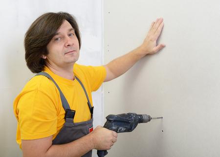 tablaroca: Hombre que usa el taladro para fijar el panel de yeso en la pared