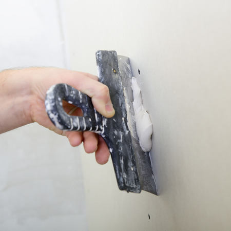 drystone: repairman works with plasterboard, plastering dry-stone wall, home improvement