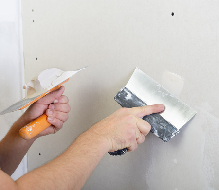 plastering: repairman works with plasterboard, plastering dry-stone wall, home improvement