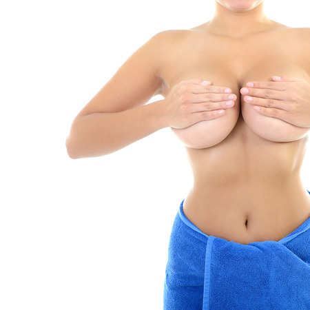 Body of beautiful woman covering her breast with hand in blue towel, over white photo