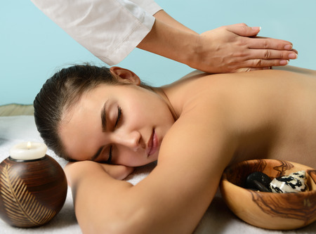 portrait of young beautiful woman in spa environment gets massage Stock Photo