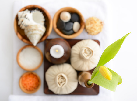 spa still life with spa herbal balls, candlestick, tulip, stones and salt in wooden bowl and white towel over white photo