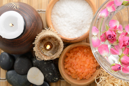 spa still life with candlestick, roses, stones and salt in wooden bowl over bamboo mat photo