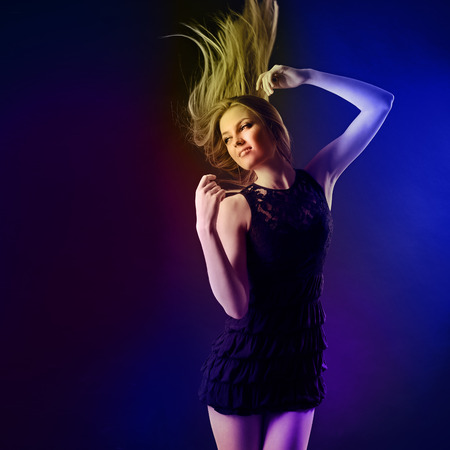 glam: Dancing party girl. Young beautiful excited woman listening music and dancing with long blond hair fly-away against dark and light vivid background