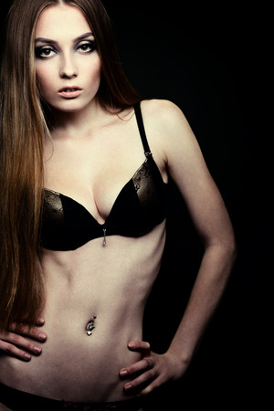 Beautiful young woman posing in bra and bikini, fashion girl over black photo