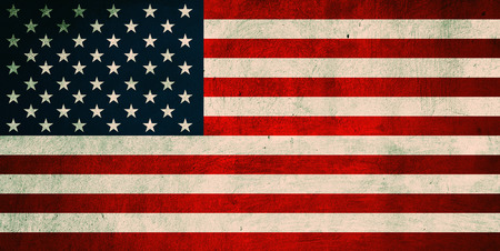 Grunge USA Flag. Background of national flag of United States of America printed on concrete wall, toned