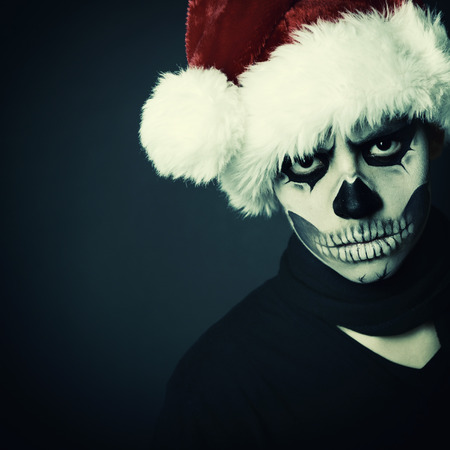 Holiday background of halloween person with terrible skull make-up in santas hat box over black background, toned photo