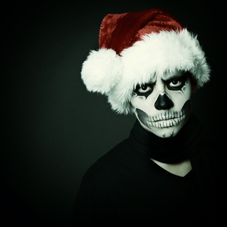 Holiday background of halloween person with terrible skull make-up in santa's hat box over black background photo