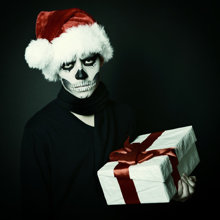 Holiday background of halloween person with terrible skull make-up in santas hat with gift box over black background photo