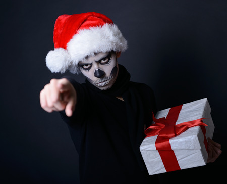 Holiday background of halloween person with terrible skull make-up in santas hat with gift box pointing at you over black background photo