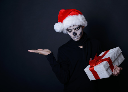 Holiday background of halloween person with terrible skull make-up in santas hat with gift box pointing at empty copyspace over black background photo