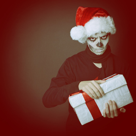 Holiday background of halloween person with terrible skull make-up in santas hat opening gift box, toned photo