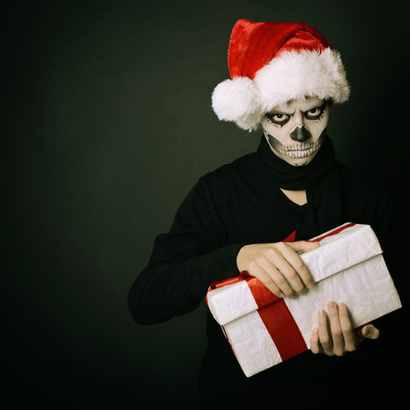 Holiday background of halloween person with terrible skull make-up in santas hat opening gift box over dark background, toned photo