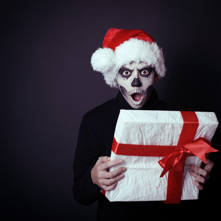Holiday background of halloween person with terrible skull make-up in santa's hat opening gift box, toned photo